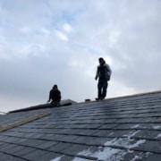 2 håndværkere står på toppen af skifer tag